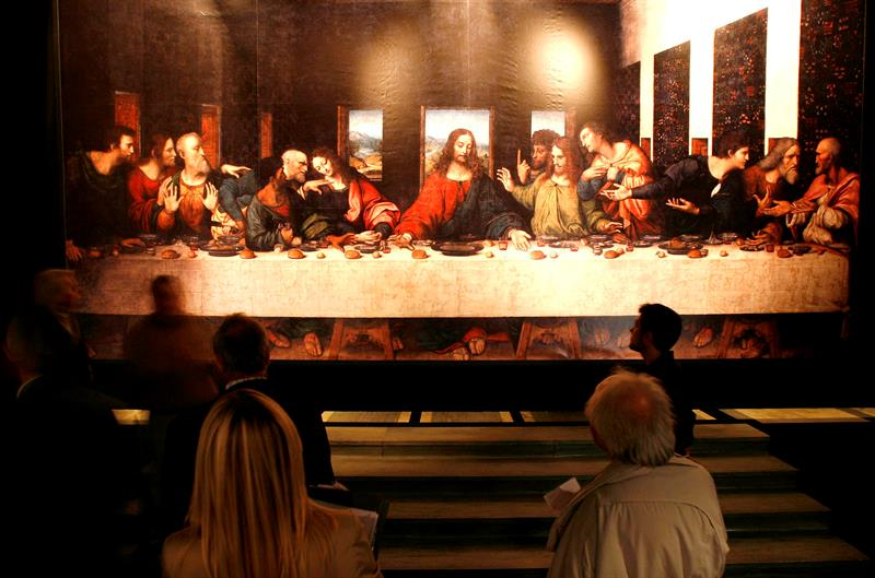 "Varias personas observan una copia de la famosa obra de Leonardo da Vinci ""La última cena""."