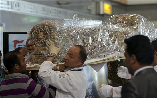 Arqueólogos portando un sarcófago