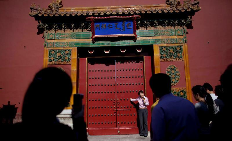 Visitantes rodean a una reportera de televisión en la entrada del Museo del Palacio de Pekín en la Ciudad Prohibida, en Pekín (China).