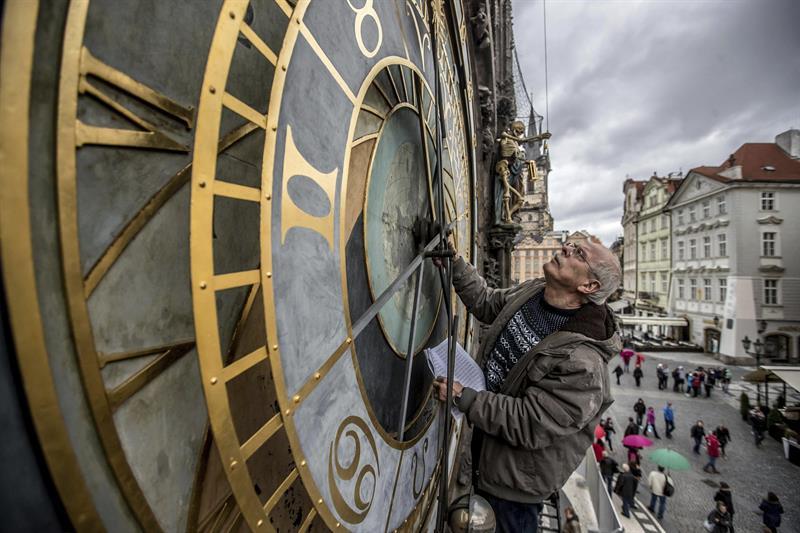El relojero Petr Skala comprueba el reloj astronómico de Praga durante unas obras de restauración en la Plaza Vieja, en Praga (República Checa).