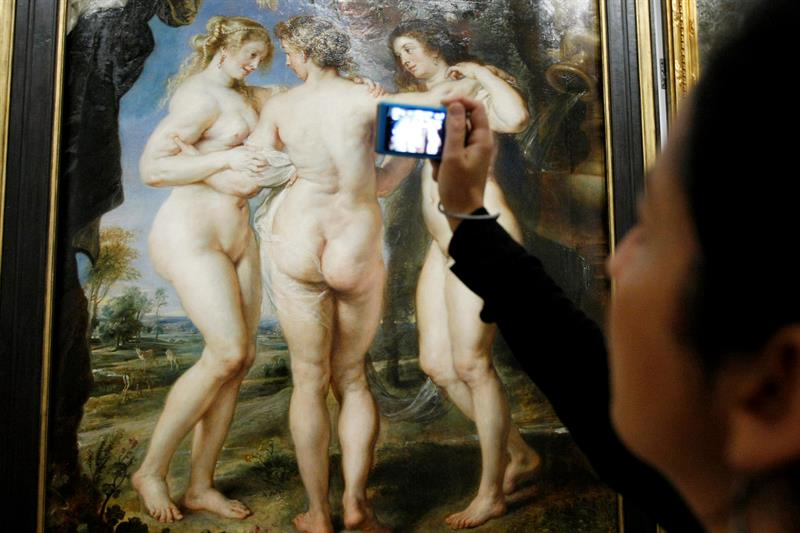 """Un visitante capta imágenes del cuadro """"Las Tres Gracias"""", de Rubens. EFE."""