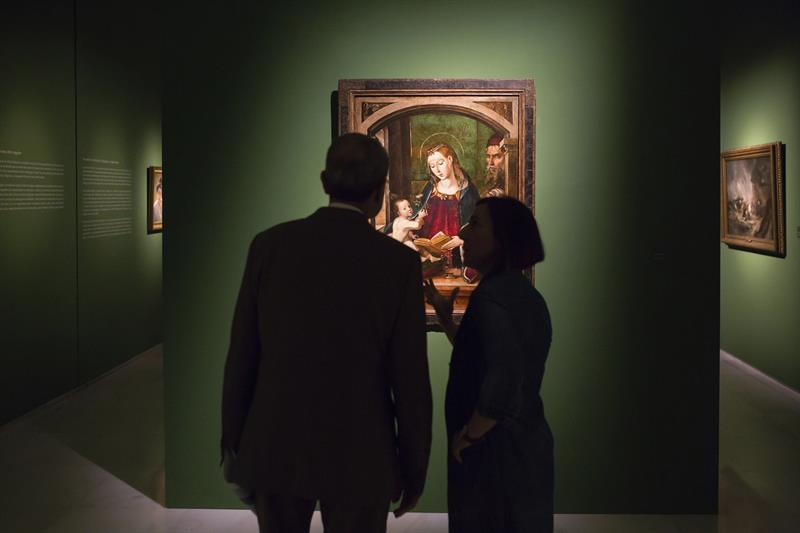 """Dos personas observan el cuadro de la """"Sagrada Familia"""" de Pedro Berruguete, que forma parte de la exposición """"La esencia de la belleza"""" de los fondos de la Fundación Godia. EFE"""